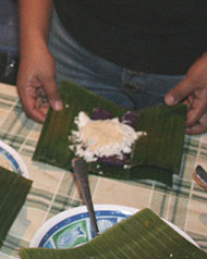 strips of puto bumbong are arranged on a piece of wilted banana leaf and garnished with grated coconut and sugar