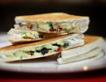 Grilled cheese sandwich with black olives and sun-dried tomatoes