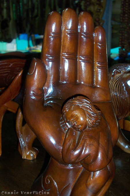 casaveneracion.com hand carved wood decor: girl resting her head on a huge hand