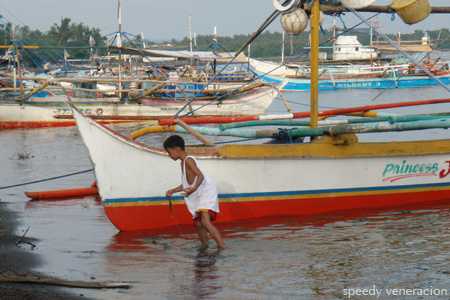 Balayan, Batangas: a young boy by a boat on the beach