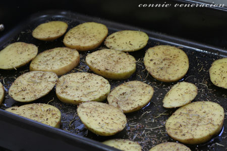 casaveneracion.com potato slices sprinkled with thyme, oregano, rosemary, salt and pepper