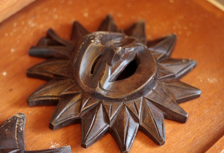 Wood sculpture of a laughing sun