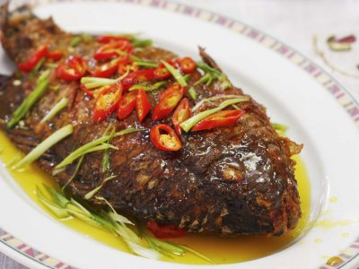 Tilapia with kalamansi sauce sprinkled with sliced chili and onion leaves