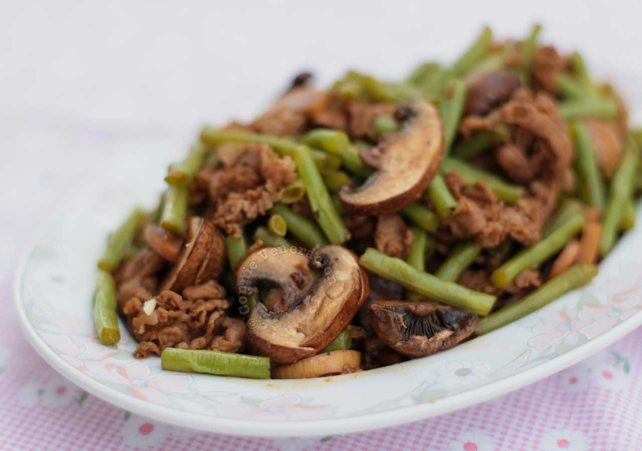 Pork, mushrooms and green beans adobo in serving plate