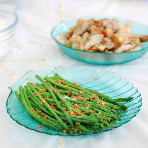 Blanched asparagus spears are blanched in salted water then tossed in garlic-infused butter. Crispy garlic bits complete the dish.
