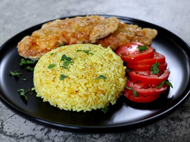 Filipino Java rice with fried fish and tomato slices on black plate