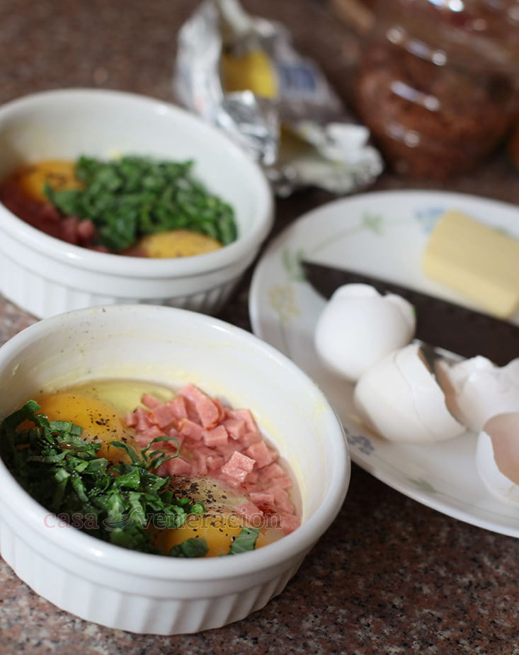 Delicious baked eggs with ham, greens and cheese