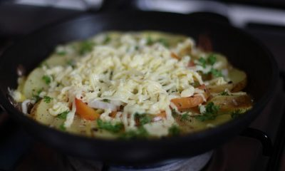 An outer circle of sliced potatoes, an inner circle of sliced tomatoes, a center of chopped bell peppers and onions. Cooked with butter. Topped with cheese.