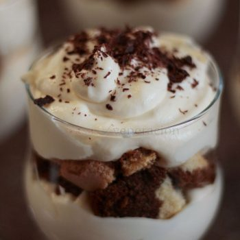 Mascarpone sweetened with sugar and made richer with eggs are dropped by tablespoonfuls into wine glasses and topped with lady fingers soaked in espresso. Another layer of mascarpone goes on top of the biscuits and the tiramisu in wine glasses are garnished with grated chocolate. It's divine.