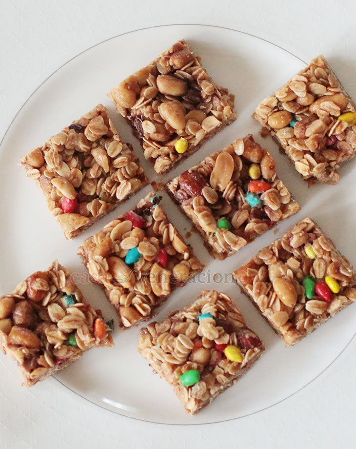 We baked granola bars. But because I cut them into squares, I call them granola squares. And because it was Sam who chose what should go into them, not only did our granola squares contain the traditional oats, nuts and honey, they also had bits of sugar-coated chocolate.