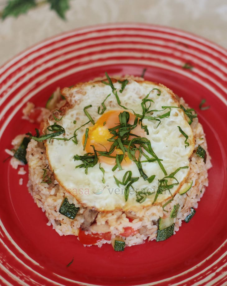 Made with pre-cooked pork, day-old rice, fresh vegetables and sweet basil, this egg-topped zucchini and tomato rice is filling, colorful and tasty to the last spoonful. It is fried rice cooked Asian-style but the flavors are more Mediterranean than Asian.