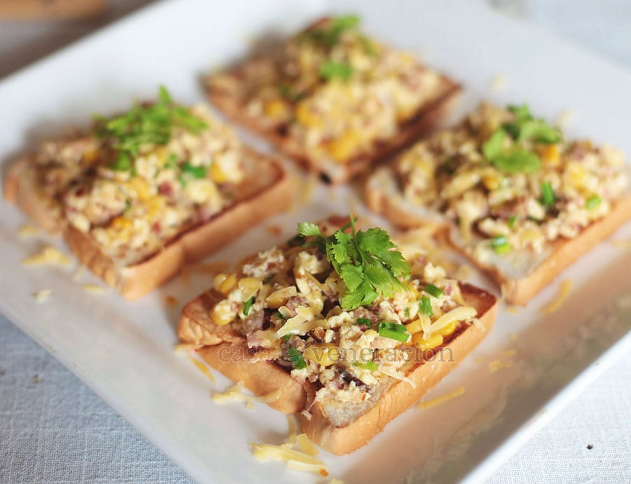 Scrambled eggs with bacon and corn on open-faced sandwiches. Sprinkled with cheese too. | casaveneracion.com