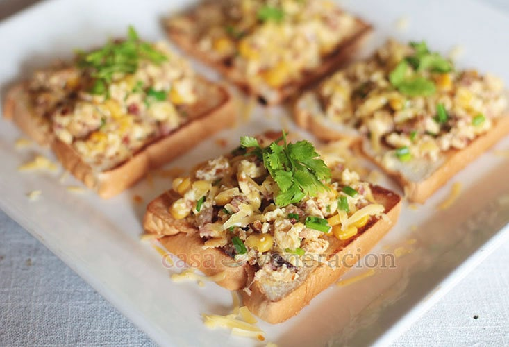 Scrambled eggs with bacon and corn on open-faced sandwiches. Sprinkled with cheese too.