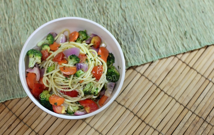 A vegan spaghetti dish with broccoli, red onion, carrot and tomatoes