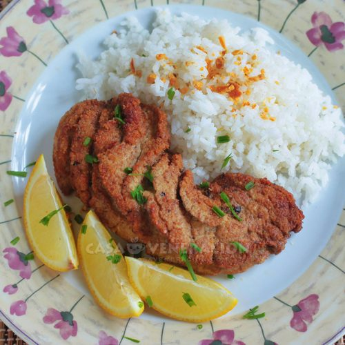 Fried fish roe with rice and lemon wedges