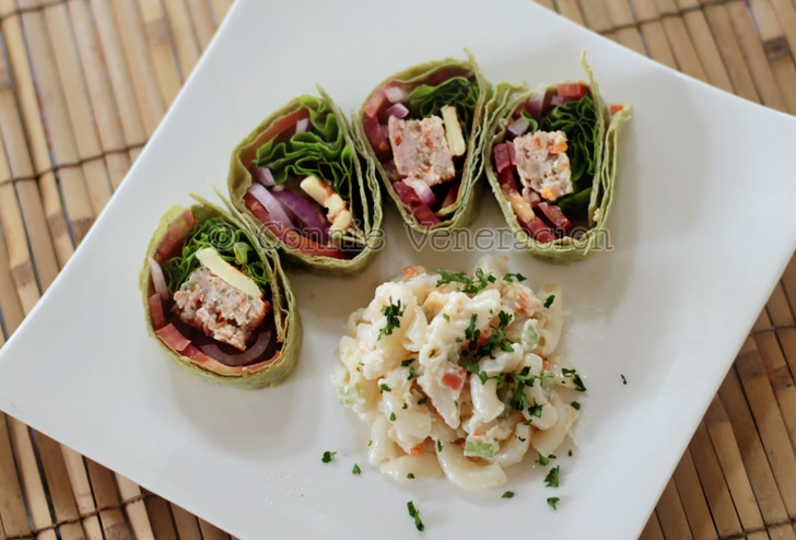 Sliced and rolled spinach tortilla stuffed with meat, vegetables and cheese. Macaroni salad on the side.