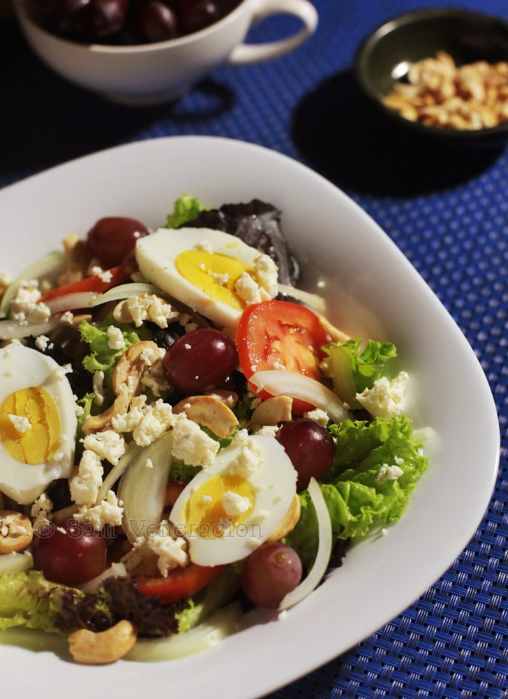 Vegetable salad with grapes, egg slices, cashew nuts and feta cheese