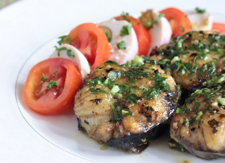 Fried fish steaks with pesto served with tomato and salted eggs