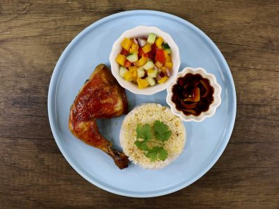 Chicken inasal, rice, salad and dipping sauce on a blue plate