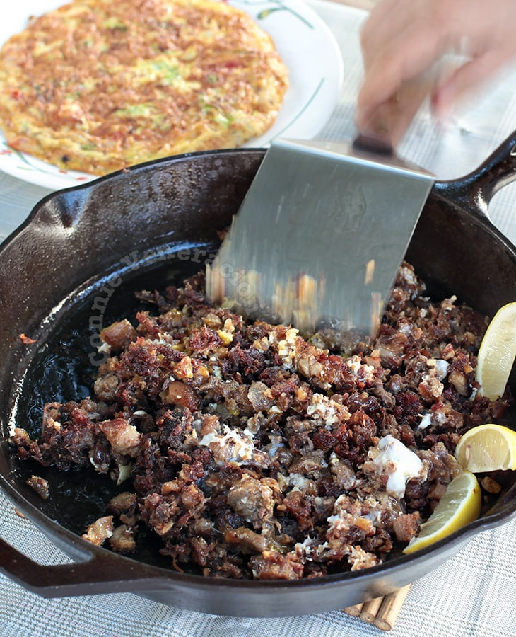 Cook store-bought sisig in cast iron pan