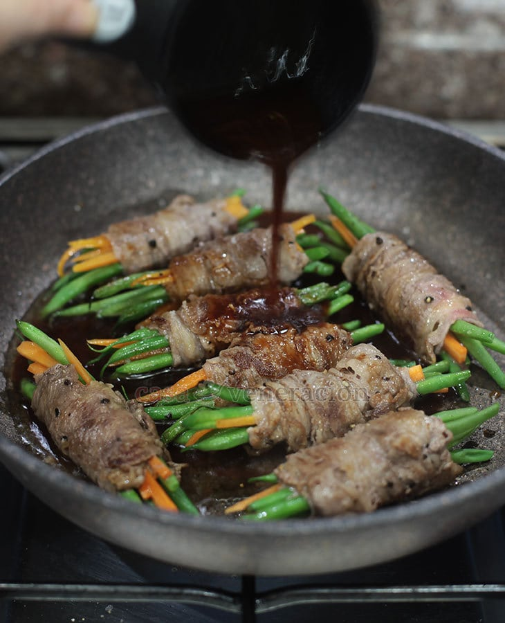 How To Cook Beef-wrapped Green Beans With Soy Ginger Sauce: Step 3 - Pour in the sauce and simmer the beef until cooked through