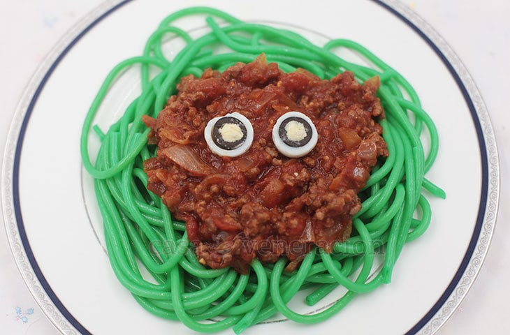 Halloween scary pasta: Slimy green noodles smothered with dark red meat sauce and topped with eyes made from quail eggs and olives.