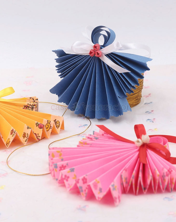 Paper, scissors, glue and ribbons are all you need to make these origami angels to hang on your Christmas tree.