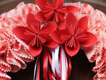 Using red construction paper, I folded origami poinsettia to spruce up my cupcake liner Christmas wreath. Click for an easy-to-follow step-by-step guide.