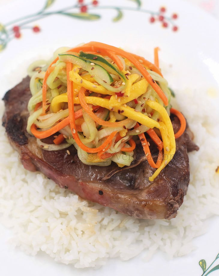 Top the cucumber and mango salad with chili lime dressing with toasted sesame seeds, serve with grilled meat and have a meal with Southeast Asian flavors.