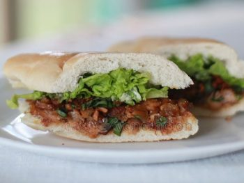 Leftover pork barbecue is chopped, reheated with barbecue sauce and used as a sandwich filling. For contrast, the meat is topped with fried shallots and basil. Lettuce completes the pork barbecue sandwiches.
