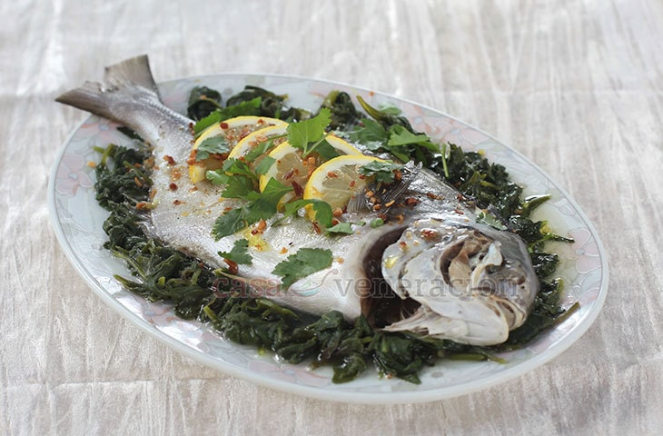 Whole fish is rubbed with salt and spices, steamed on a bed of wilted spinach then drizzled with extra virgin olive oil and lemon juice before serving. Steamed fish with lemon and olive oil is simple and elegant.