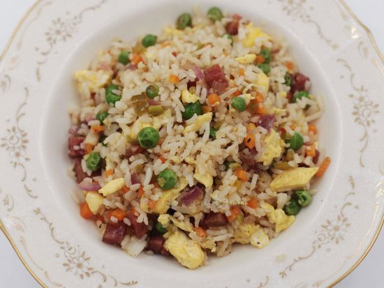 The secret to a good Chinese-style fried rice is to start by creating a flavor base. The vegetables are stir fried, the cooked meat is added followed by the rice and, finally, the eggs. Season every step of the way.
