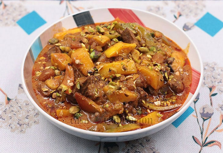 Beef short ribs cooked in yogurt with cayenne, turmeric, paprika and golden raisins, and garnished with fresh mangoes and toasted pistachio