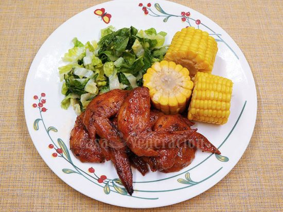 Baked Cajun chicken wings with boiled corn and simple vegetable salad