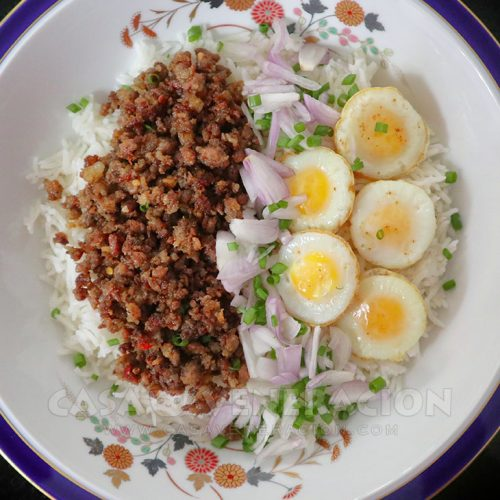 Sausage meat and quail eggs over rice
