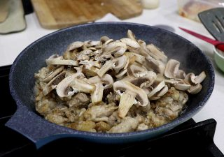 Adding sliced mushrooms to browned chicken fillets