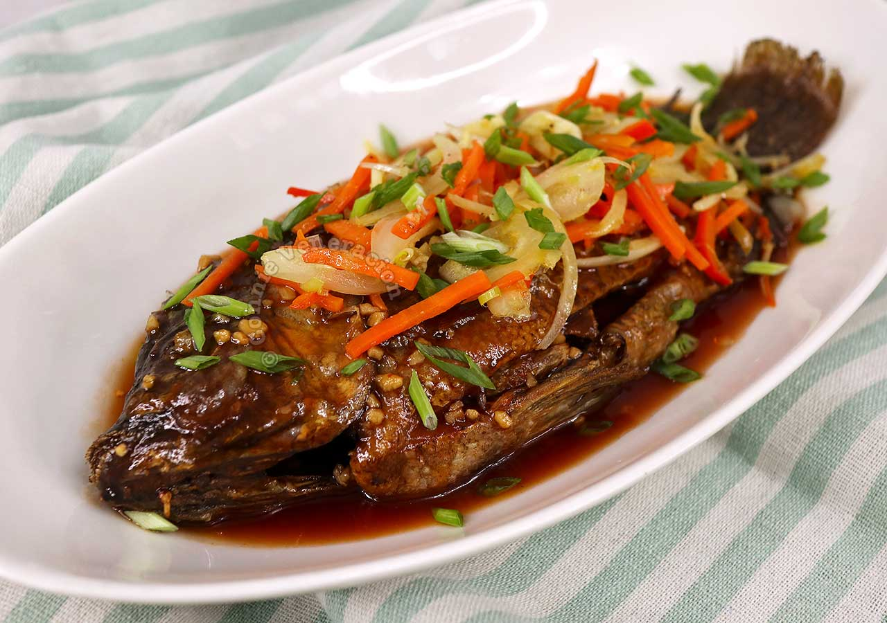 Tilapia escabeche topped with julienned vegetables and thinly sliced scallions