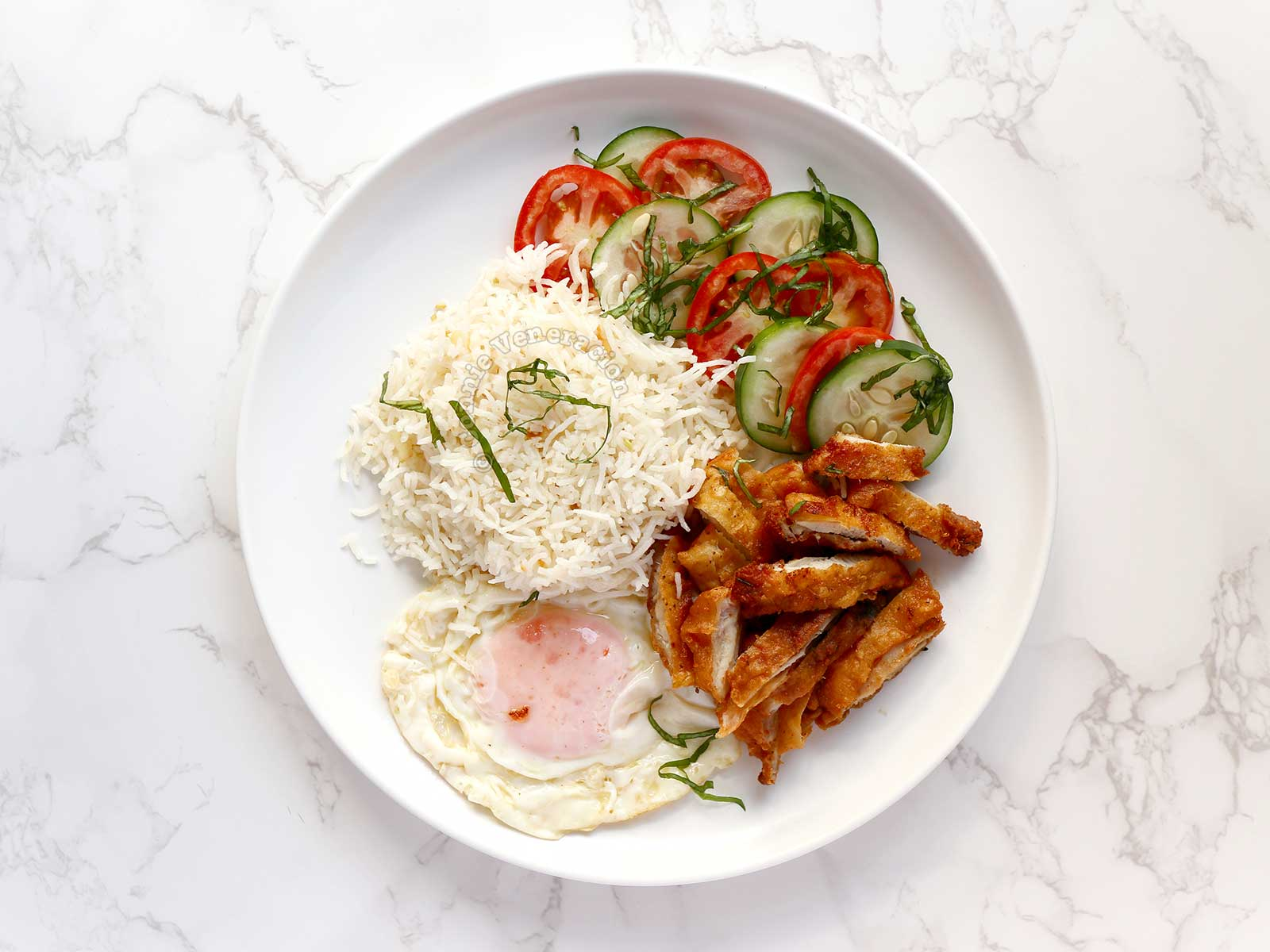 Chiksilog (Fried Chicken, Fried Rice and Egg) Served with Sliced Cucumber and Tomato Sprinkled with Fresh Basil